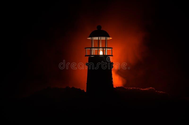 Τρομακτικός σκοτεινός δυσοίωνος φάρος πίσω από ένα κόκκινο υπόβαθρο πυρκαγιάς Φάρος dusk/στο φάρο φάρων ηλιοβασιλέματος στο ηλιοβ στοκ φωτογραφία με δικαίωμα ελεύθερης χρήσης