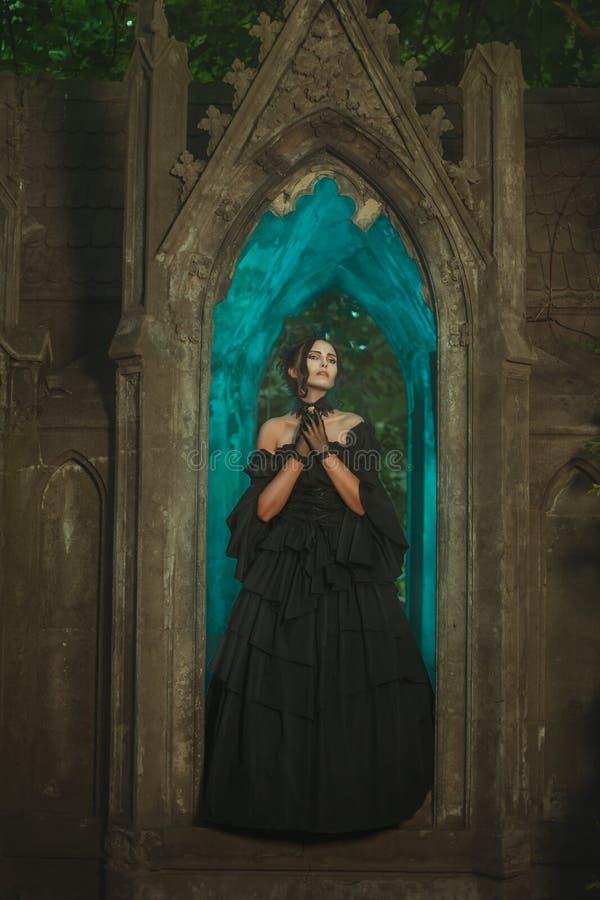 Τρομακτικό κορίτσι που στέκεται τη νύχτα στο κάστρο στοκ εικόνες