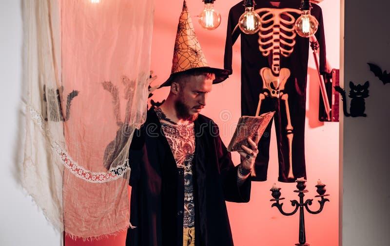Τρομακτικό hipster με τη γενειάδα στο καπέλο μαγισσών και το πουκάμισο καρό r Αποκριές, εορτασμός διακοπών στοκ εικόνες