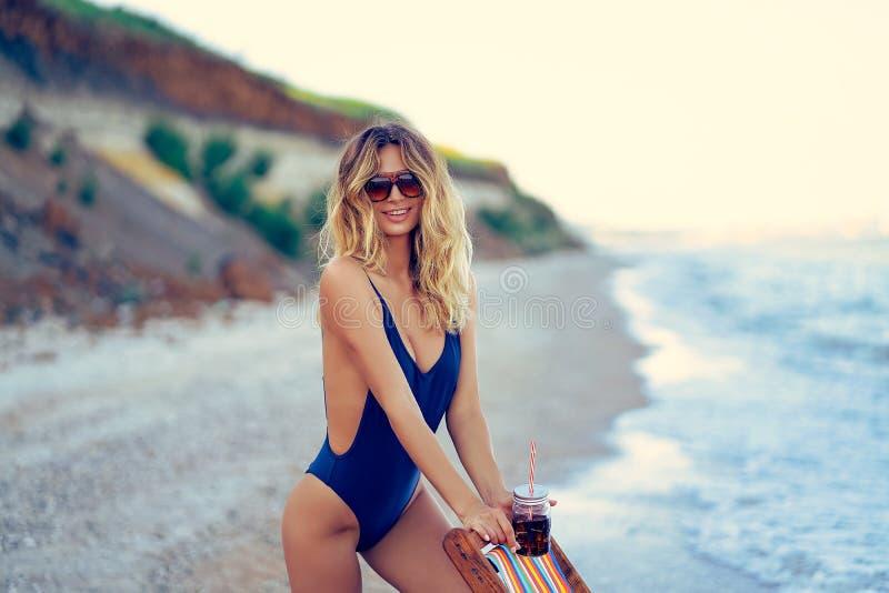 Τρομερή ξανθή γυναίκα ομορφιάς στα γυαλιά ηλίου, χαλάρωση μαγιό στην παραλία και ποτά coctail r στοκ εικόνες