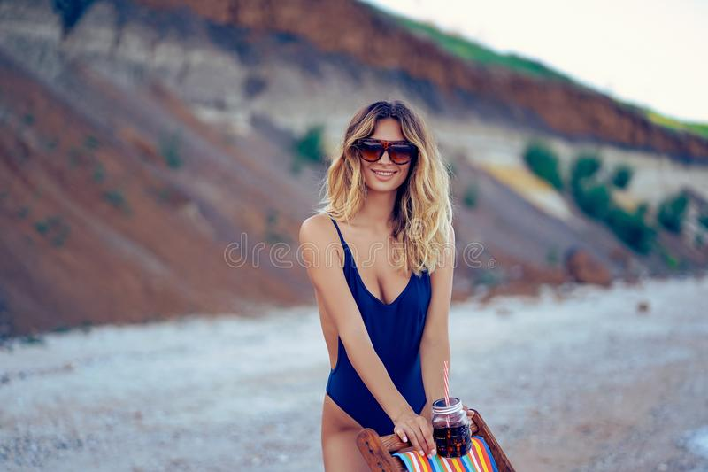 Τρομερή ξανθή γυναίκα ομορφιάς στα γυαλιά ηλίου, χαλάρωση μαγιό στην παραλία και ποτά coctail r στοκ φωτογραφία