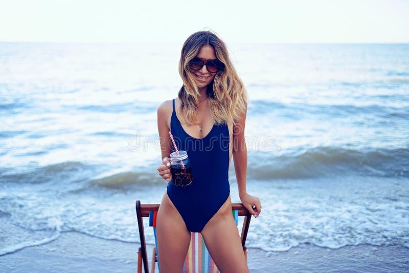 Τρομερή ξανθή γυναίκα ομορφιάς στα γυαλιά ηλίου, χαλάρωση μαγιό στην παραλία και ποτά coctail r στοκ φωτογραφίες με δικαίωμα ελεύθερης χρήσης