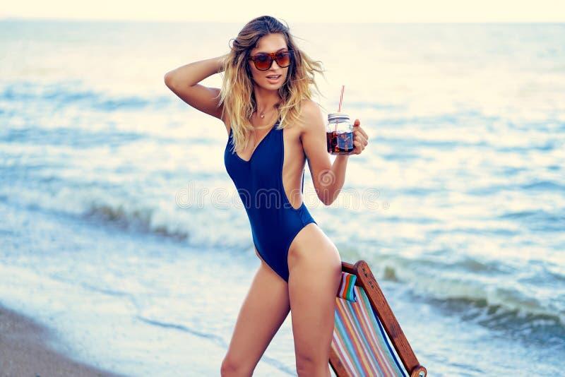 Τρομερή ξανθή γυναίκα ομορφιάς στα γυαλιά ηλίου, χαλάρωση μαγιό στην παραλία και ποτά coctail r στοκ εικόνες με δικαίωμα ελεύθερης χρήσης