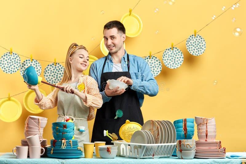 Τρομεροί νέοι που αφαιρούν τα τρόφιμα από τα βρώμικα πιάτα στοκ εικόνα