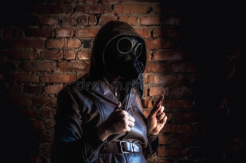 Τρομερός γιατρός πανούκλας στο κόκκινο τούβλο φόντο Μανιακός μασκοφόρος με νυστέρι και ψαλίδι Αποκριές και τρόμος στοκ εικόνες