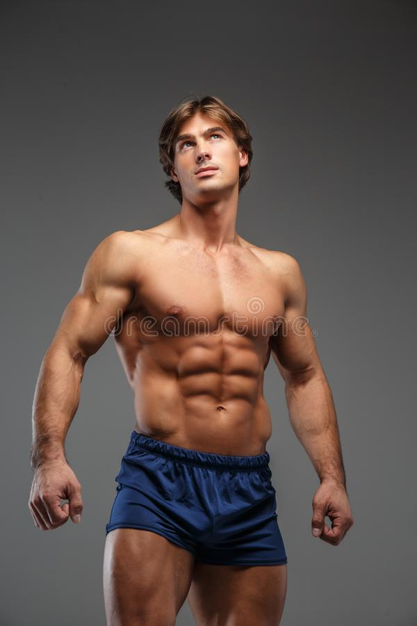 Τρομερός γυμνόστηθος bodybuilder στα μπλε σορτς στοκ φωτογραφία με δικαίωμα ελεύθερης χρήσης