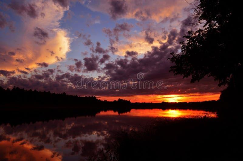 Τρομερός πυροβολισμός ενός θαυμάσιου ηλιοβασιλέματος πέρα από τη λίμνη στοκ φωτογραφία με δικαίωμα ελεύθερης χρήσης