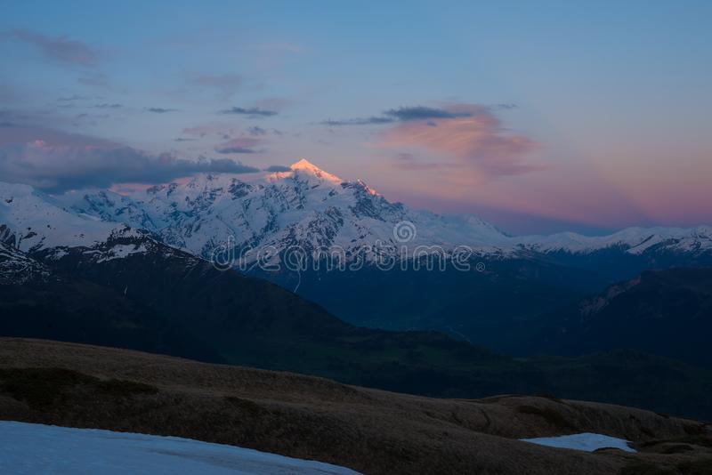 Τρομερό ζωηρόχρωμο ηλιοβασίλεμα πέρα από τη χιονοσκεπή αιχμή βουνών στοκ εικόνες