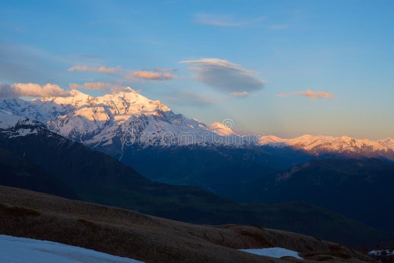 Τρομερό ηλιοβασίλεμα πέρα από τις χιονοσκεπείς αιχμές βουνών στοκ εικόνες με δικαίωμα ελεύθερης χρήσης