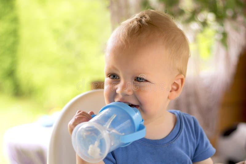 Τρομερό σγουρό blondy υπαίθριο και πόσιμο νερό συνεδρίασης μικρών παιδιών στοκ φωτογραφίες