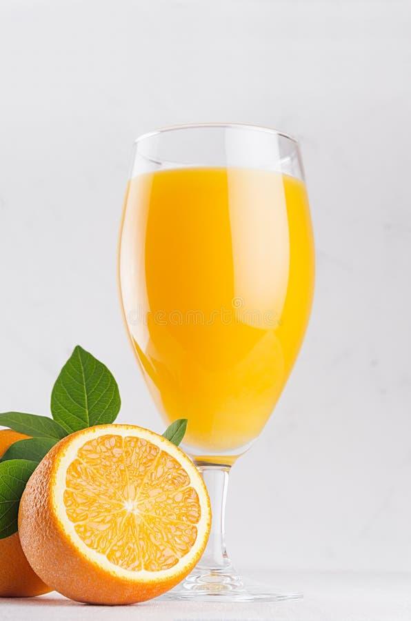 Τροπικός κίτρινος χυμός εσπεριδοειδών wineglass κομψότητας στην κινηματογράφηση σε πρώτο πλάνο με τα ώριμα πορτοκάλια και τα πράσ στοκ εικόνες