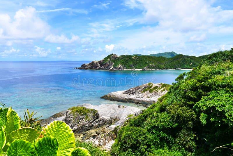 Τροπικός παράδεισος των πράσινων λόφων, της άσπρης άμμου, της τυρκουάζ θάλασσας και του βαθιά μπλε ηλιόλουστου ουρανού σε Zamami, στοκ εικόνα