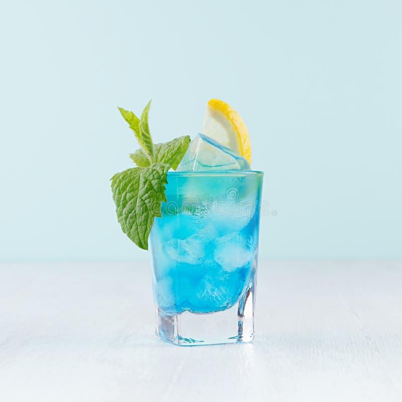 Τροπικό μπλε ποτό οινοπνεύματος παραλιών - το ποτό του Κουρασάο, φέτα λεμονιών, πάγος, μέντα μέσα το βλασταημένο γυαλί στο πράσιν στοκ φωτογραφία με δικαίωμα ελεύθερης χρήσης