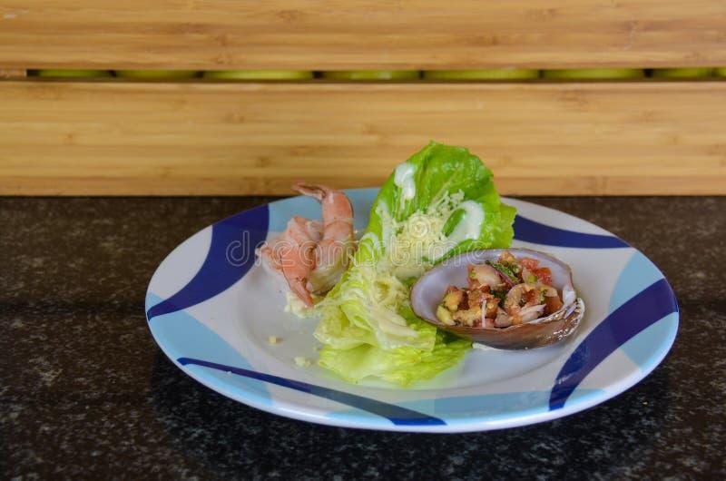Τροπικό πιάτο των γαρίδων σε ένα μαλάκιο με τη σαλάτα στοκ φωτογραφίες