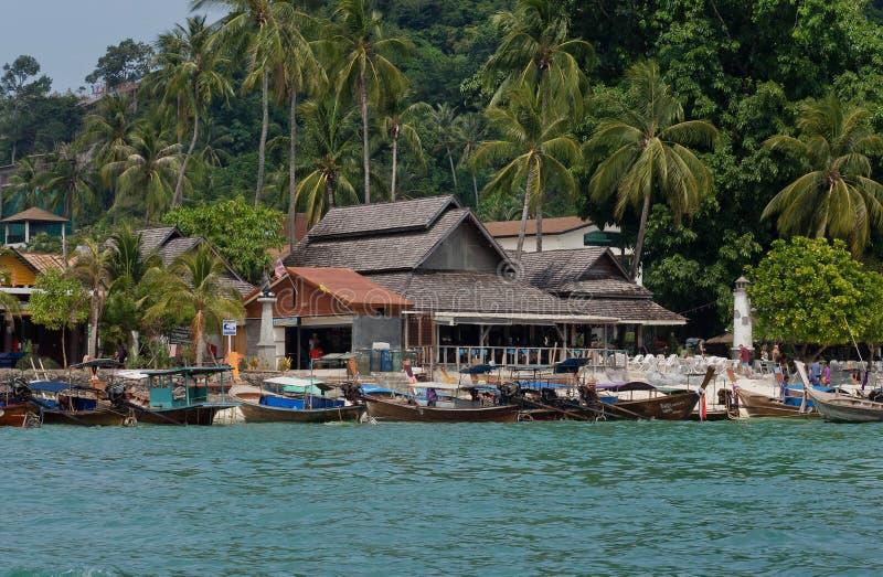 Τροπικό χωριό με τις λέμβους πλοίου και τα ξύλινα σπίτια κάτω από τους φοίνικες στοκ φωτογραφία με δικαίωμα ελεύθερης χρήσης