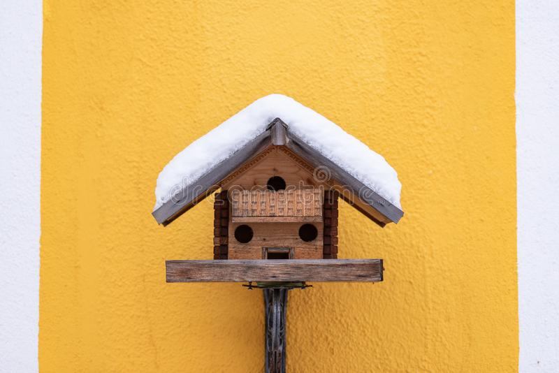 Τροφοδότης του σπιτικού ξύλινου πουλιού στον κίτρινο τοίχο το χειμώνα, κάτω από το χιόνι στοκ εικόνα