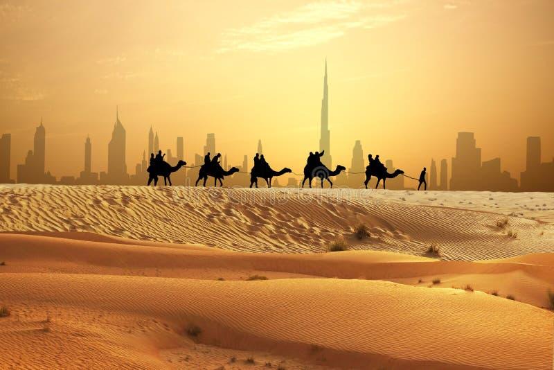 Τροχόσπιτο καμηλών στους αμμόλοφους άμμου στο αραβικό επιδόρπιο με τον ορίζοντα του Ντουμπάι στο ηλιοβασίλεμα στοκ φωτογραφία με δικαίωμα ελεύθερης χρήσης