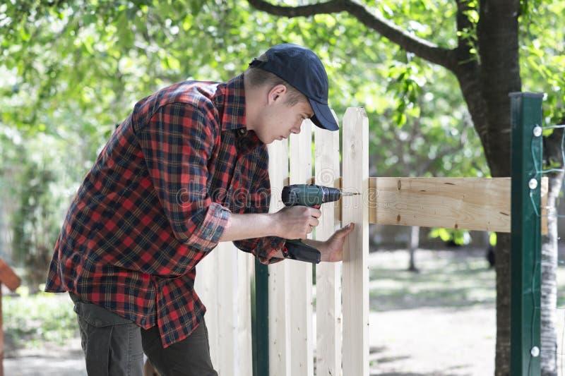 Τρυπάνι-κίνηση εκμετάλλευσης νεαρών άνδρων Εργασίες ξυλουργών στοκ φωτογραφία