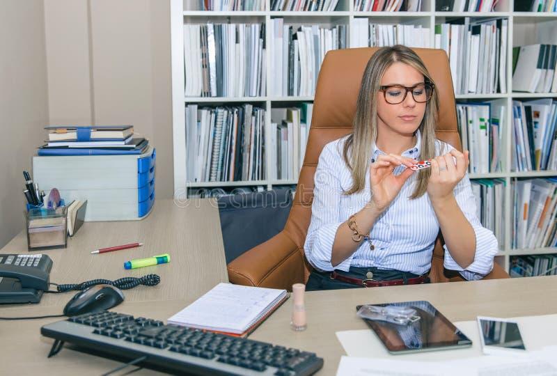 Τρυπημένα ξανθά γυαλίζοντας καρφιά γραμματέων στο γραφείο στοκ φωτογραφίες