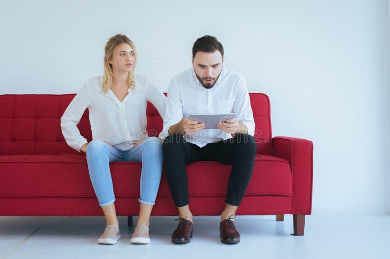 Τρυπημένη και συνεδρίαση εραστών ζευγών αμέλειας στον καναπέ στο καθιστικό μαζί, οικογενειακά ζητήματα στοκ εικόνα