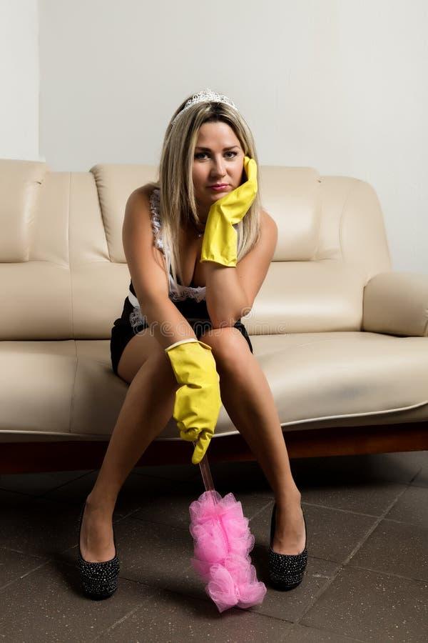Τρυπημένη συνεδρίαση γυναικών ή νοικοκυρών σε έναν κύριο καναπέ με τα λαστιχένια γάντια στοκ φωτογραφία