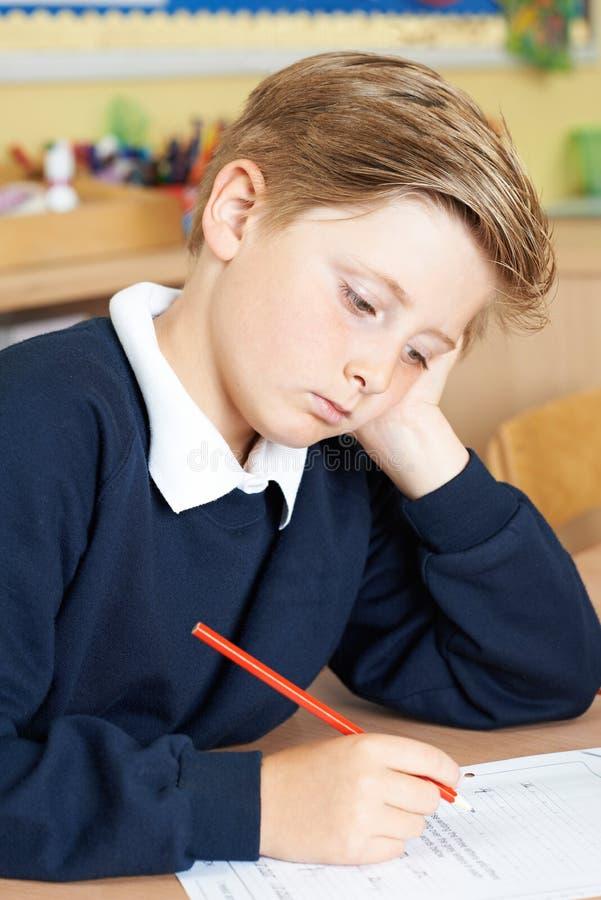 Τρυπημένος αρσενικός μαθητής δημοτικού σχολείου στο γραφείο στοκ εικόνες με δικαίωμα ελεύθερης χρήσης