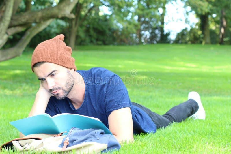Τρυπημένος σπουδαστής που διαβάζει το σημειωματάριό του στην πανεπιστημιούπολη στοκ εικόνες