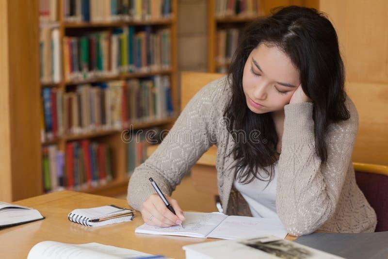 Τρυπημένος σπουδαστής σε μια εκμάθηση βιβλιοθηκών στοκ φωτογραφία με δικαίωμα ελεύθερης χρήσης