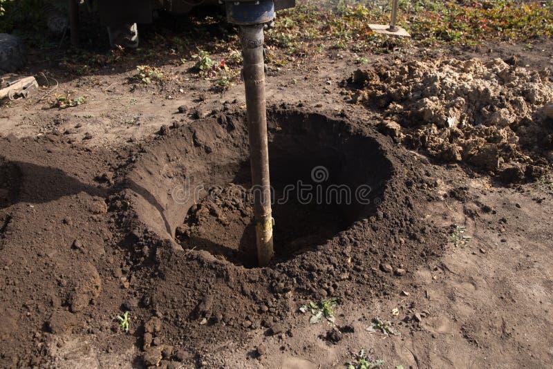 Τρυπώντας με τρυπάνι έδαφος τρυπανιών στοκ εικόνες