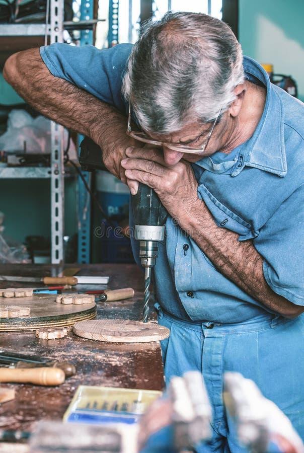 Τρυπώντας με τρυπάνι ξύλο επιπλοποιών στον πάγκο εργασίας στοκ εικόνα