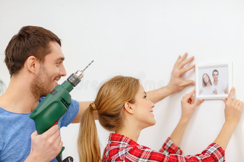 Τρυπώντας με τρυπάνι τρύπα ζευγών χαμόγελου στον τοίχο στο σπίτι στοκ φωτογραφίες