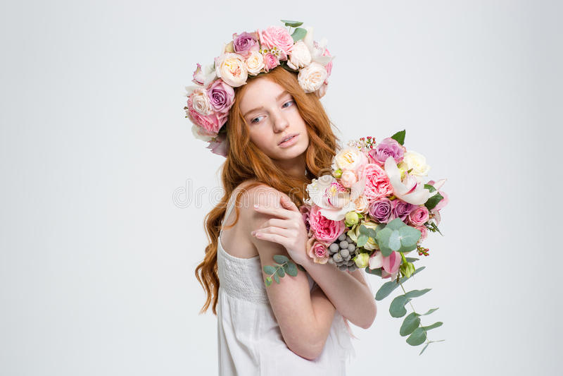Τρυφερή γοητευτική γυναίκα στην τοποθέτηση στεφανιών με την ανθοδέσμη των λουλουδιών στοκ εικόνα