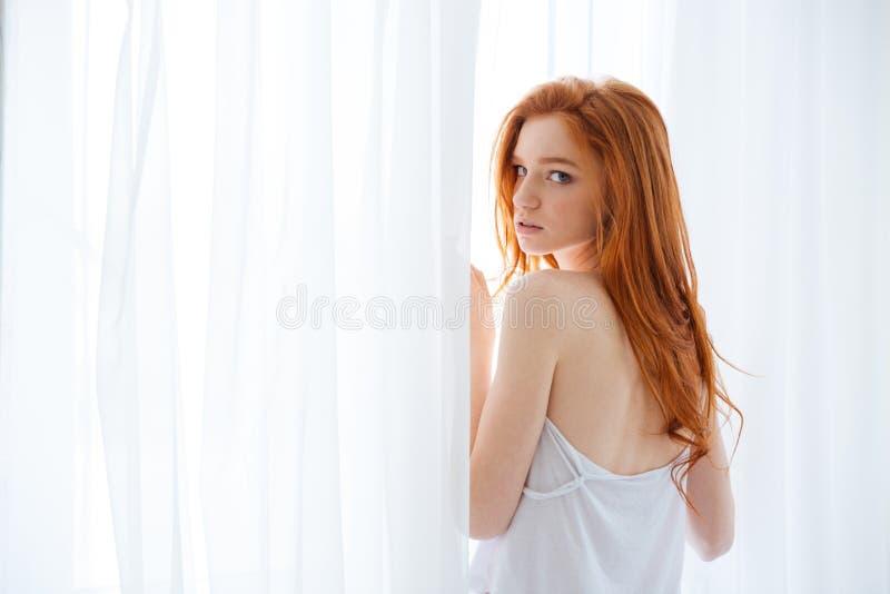 Τρυφερή γυναίκα που στέκεται κοντά στο παράθυρο στοκ φωτογραφίες με δικαίωμα ελεύθερης χρήσης