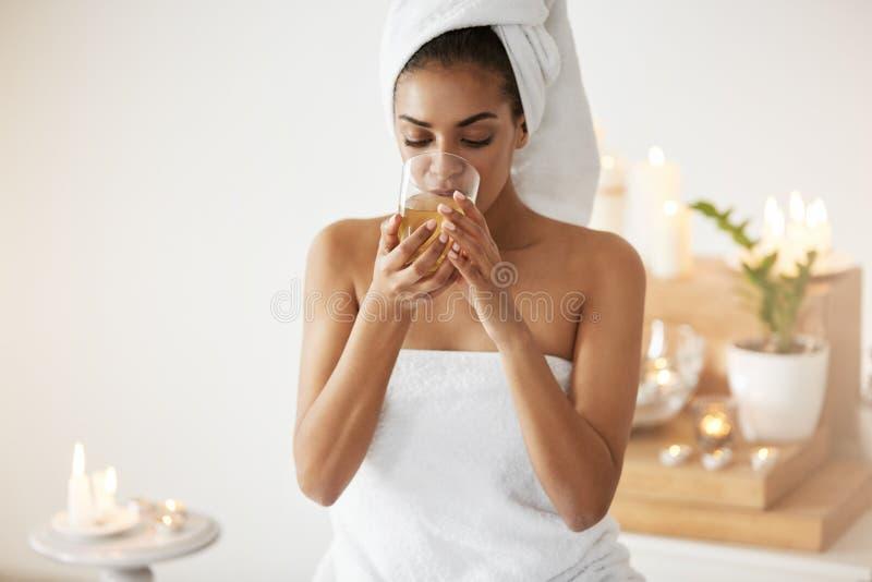 Τρυφερό αφρικανικό κορίτσι με την πετσέτα στο επικεφαλής τσάι κατανάλωσης που στηρίζεται στο σαλόνι SPA στοκ φωτογραφίες με δικαίωμα ελεύθερης χρήσης