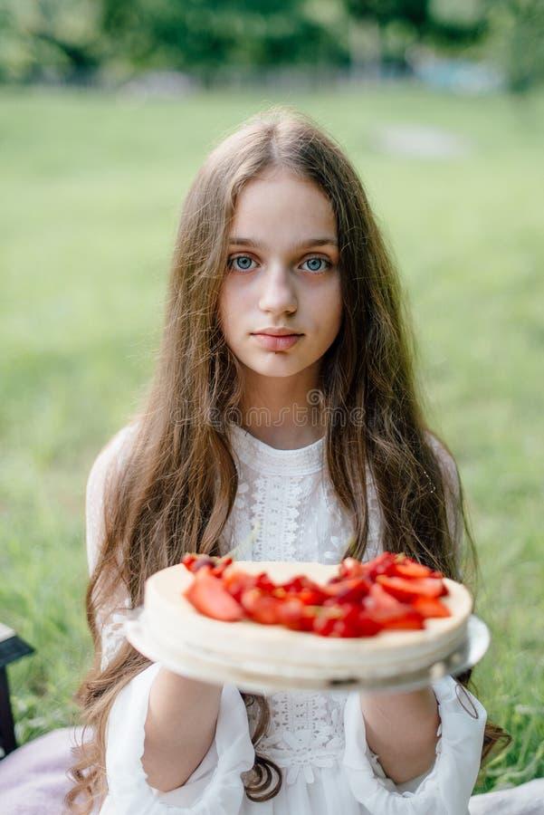 Τρυφερό κορίτσι με τα μπλε μάτια που κρατούν μαλακό γλυκό cheesecake φραουλών στοκ φωτογραφία
