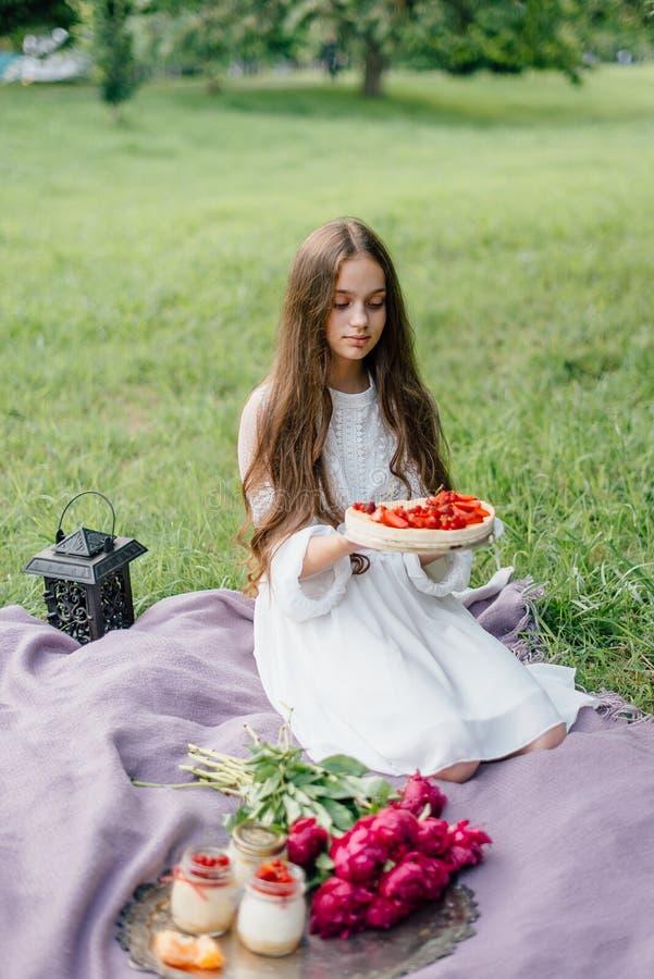 Τρυφερό κορίτσι σε ένα πικ-νίκ με γλυκά cheesecake και τα επιδόρπια στοκ φωτογραφίες
