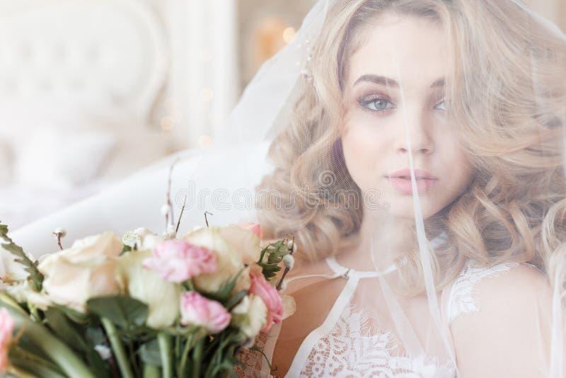 Τρυφερό πορτρέτο μιας όμορφης νύφης κάτω από μια ανθοδέσμη εκμετάλλευσης πέπλων στοκ φωτογραφία