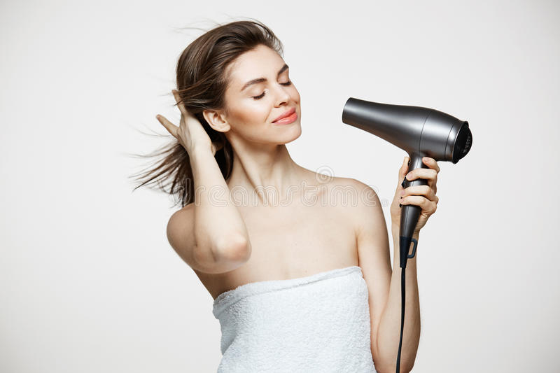 Τρυφερό όμορφο κορίτσι brunette στην ξεραίνοντας τρίχα πετσετών που χαμογελά πέρα από το άσπρο bakground ιδιαίτερες προσοχές Beau στοκ εικόνες με δικαίωμα ελεύθερης χρήσης