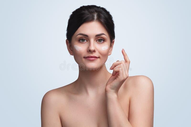 Τρυφερό brunette με την κρέμα στο πρόσωπο στοκ εικόνες