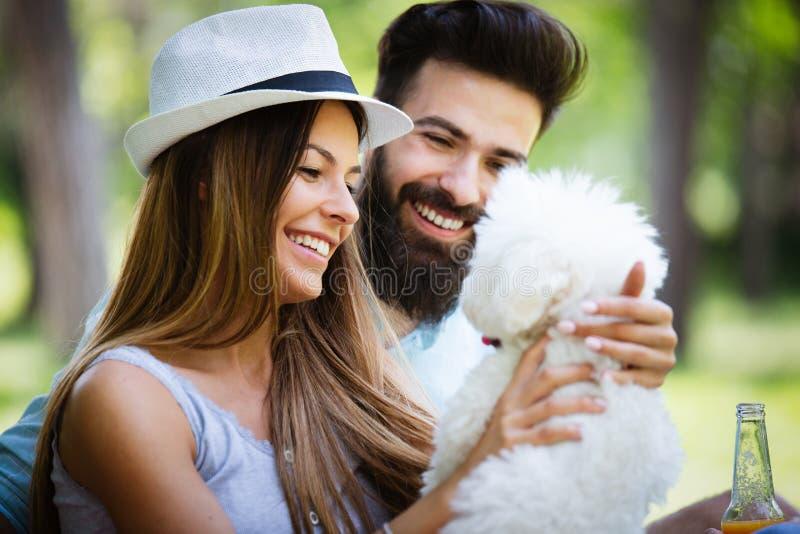 Τρόπος ζωής, ευτυχές ζεύγος που στηρίζεται σε ένα πικ-νίκ στο πάρκο με ένα σκυλί στοκ εικόνα