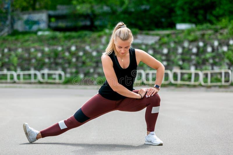 Τρόπος ζωής ικανότητας Το νέο ζέσταμα γυναικών πρίν εκπαιδεύει να κάνει ασκεί για να τεντώσει τους μυς και τις ενώσεις της Workou στοκ φωτογραφία