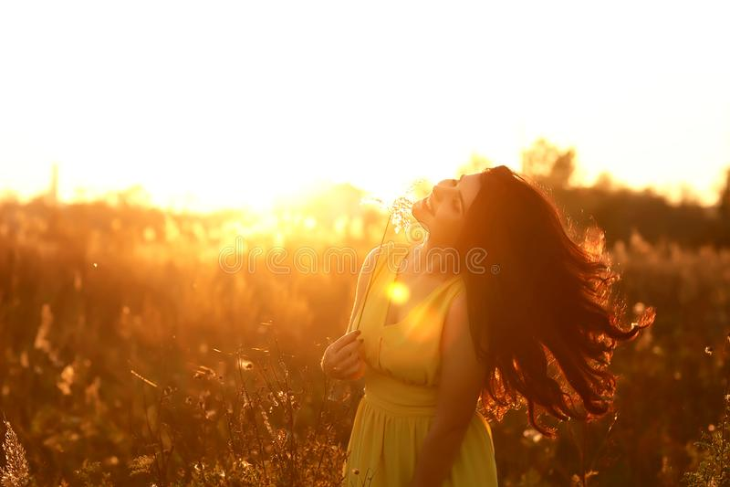 Τρόπος ζωής μόδας, πορτρέτο της όμορφης νέας γυναίκας με τη μακριά σκοτεινή τρίχα αναδρομικά φωτισμένη στο ηλιοβασίλεμα υπαίθρια  στοκ εικόνα