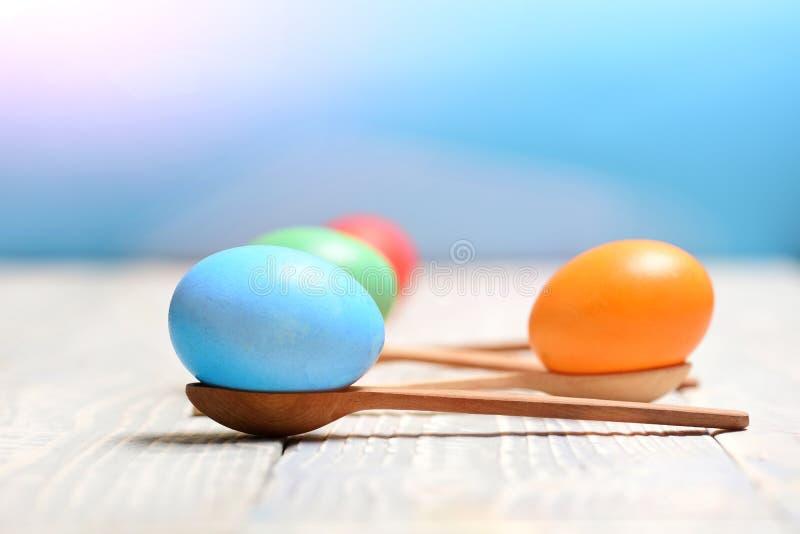 Τρόφιμα διακοπών Πάσχας, ζωηρόχρωμα χρωματισμένα αυγά στα ξύλινα κουτάλια στοκ εικόνα