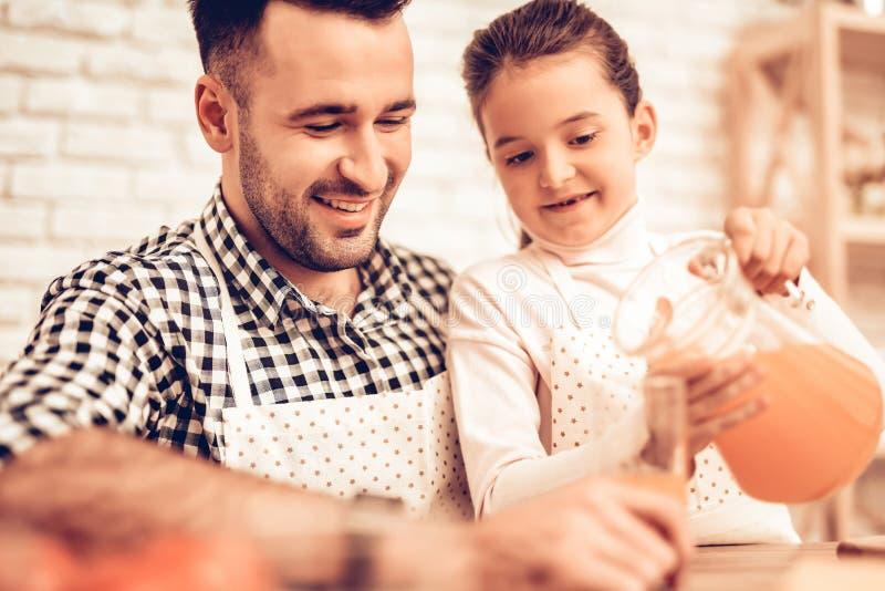 Τρόφιμα μαγείρων στο σπίτι Κόρη τροφών πατέρων Χύστε το χυμό στο ποτήρι οικογένεια ευτυχής πατέρας s ημέρας Μαγείρεμα κοριτσιών κ στοκ εικόνα