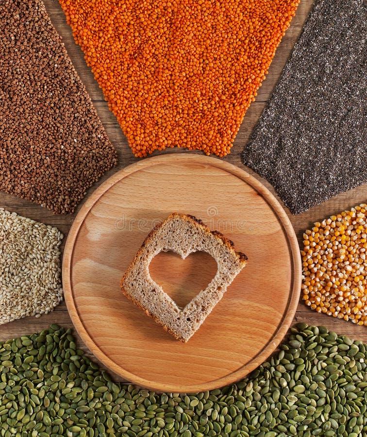 Τρόφιμα με την αγάπη Διαμορφωμένη καρδιά τρύπα στη φέτα ψωμιού που περιβάλλεται από τα σιτάρια στοκ εικόνα με δικαίωμα ελεύθερης χρήσης