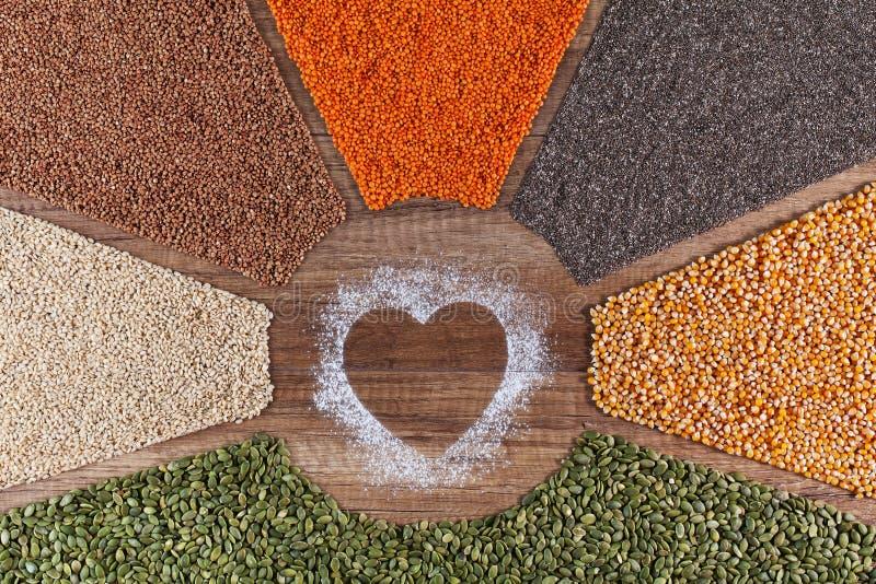 Τρόφιμα με την αγάπη - το φυτό βάσισε τη διαφοροποιημένη έννοια διατροφής με τα ζωηρόχρωμους σιτάρια και τους σπόρους στοκ φωτογραφία με δικαίωμα ελεύθερης χρήσης