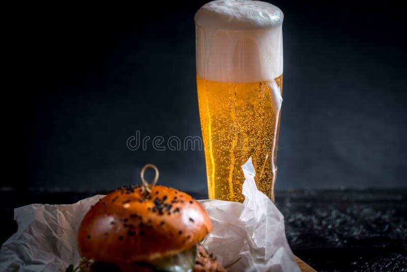 Τρόφιμα οδών Μεγάλο burger με τα ποτήρια της ελαφριάς μπύρας Σε μια ξύλινη ανασκόπηση στοκ φωτογραφία με δικαίωμα ελεύθερης χρήσης