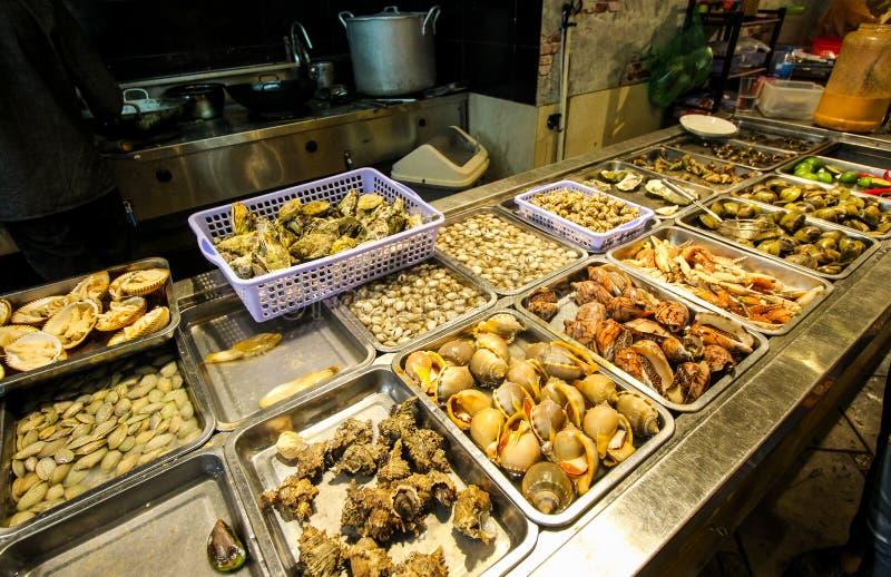 Τρόφιμα οδών τη νύχτα στο Βιετνάμ Εύγευστα θαλασσινά για τον τουρίστα στην αγορά οδών Φρέσκες κοχύλια και musles κατάταξη στοκ εικόνα