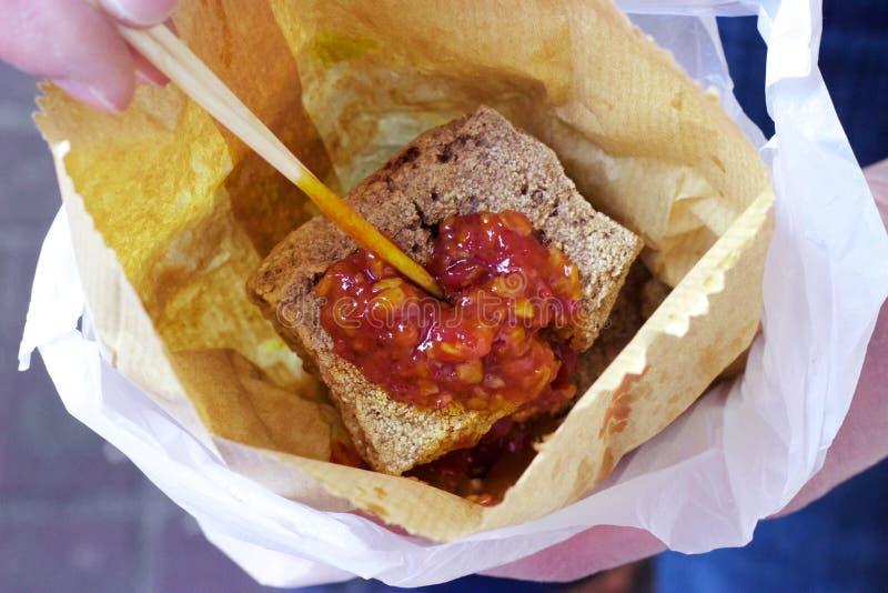 Τρόφιμα οδών Χονγκ Κονγκ: Tofu Stinky, σάλτσα τσίλι, τσάντα εγγράφου στοκ φωτογραφίες