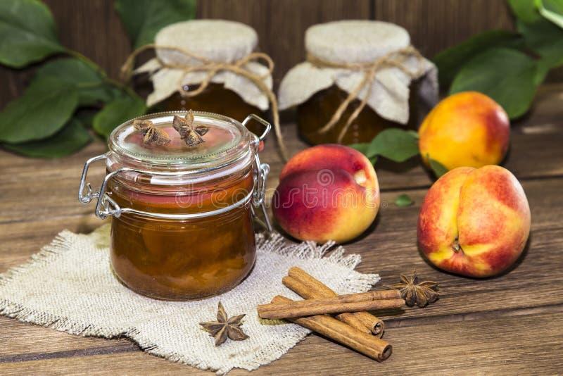Τρόφιμα Σπιτικά κονσερβοποιημένα φρούτα στα δοχεία Μαρμελάδα ροδάκινων φρούτων και φρέσκο ρ στοκ φωτογραφία